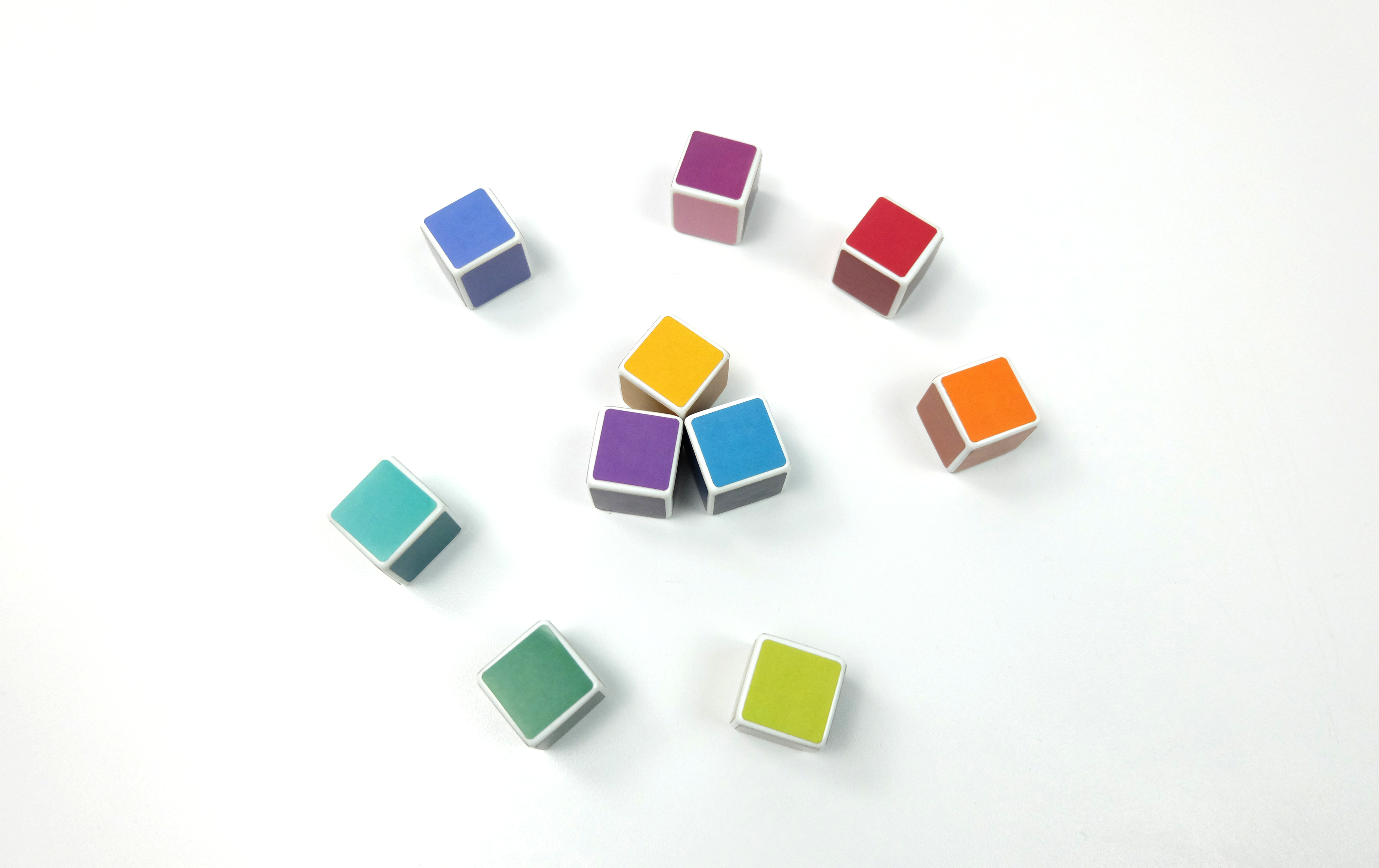 Three colorful dice are displayed together inside of a larger ring of colorful dice arranged in a color wheel on a white table.
