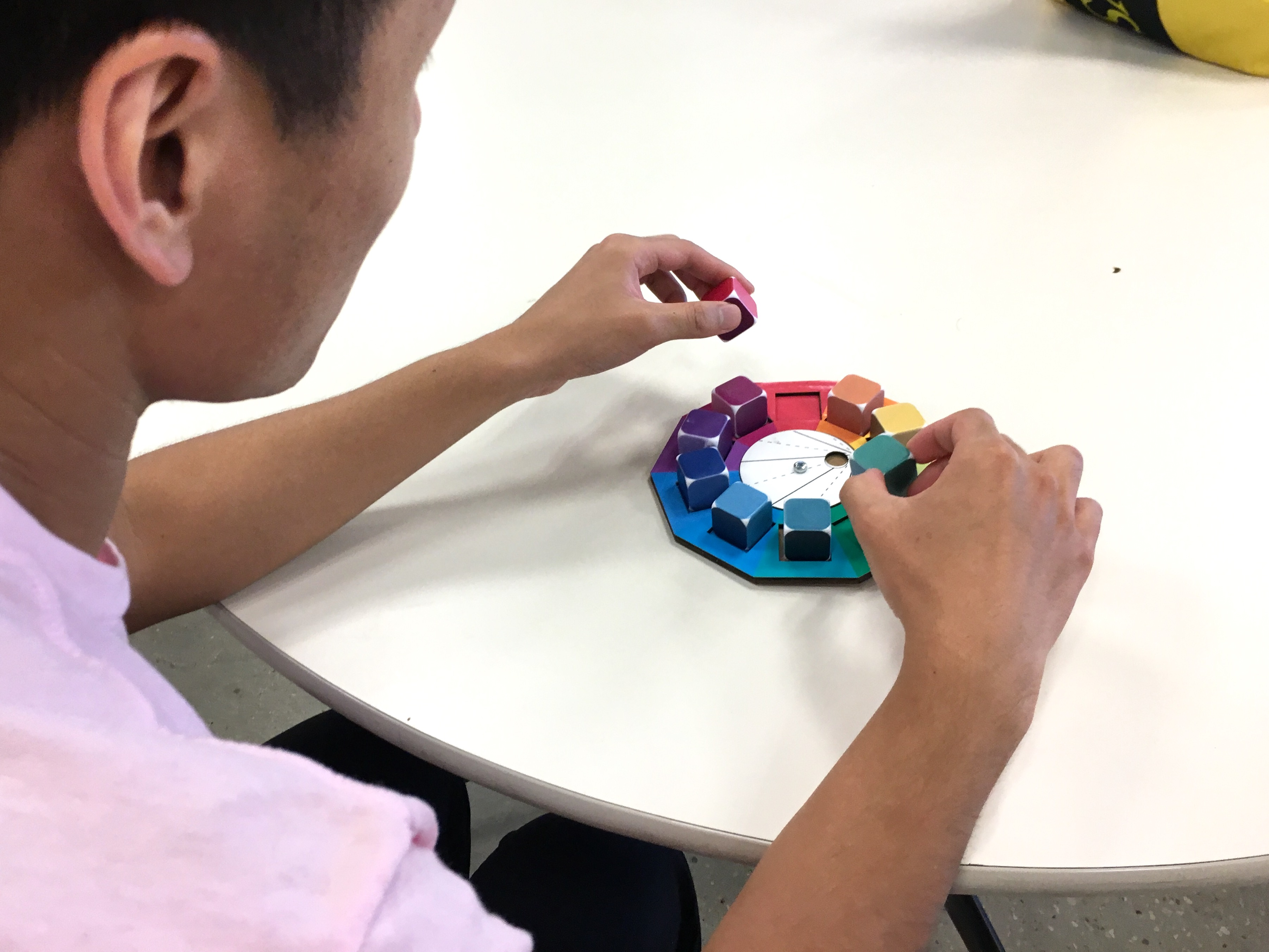 A person picks up colorful dice on a cardboard prototype of a spinning color wheel, testing it.