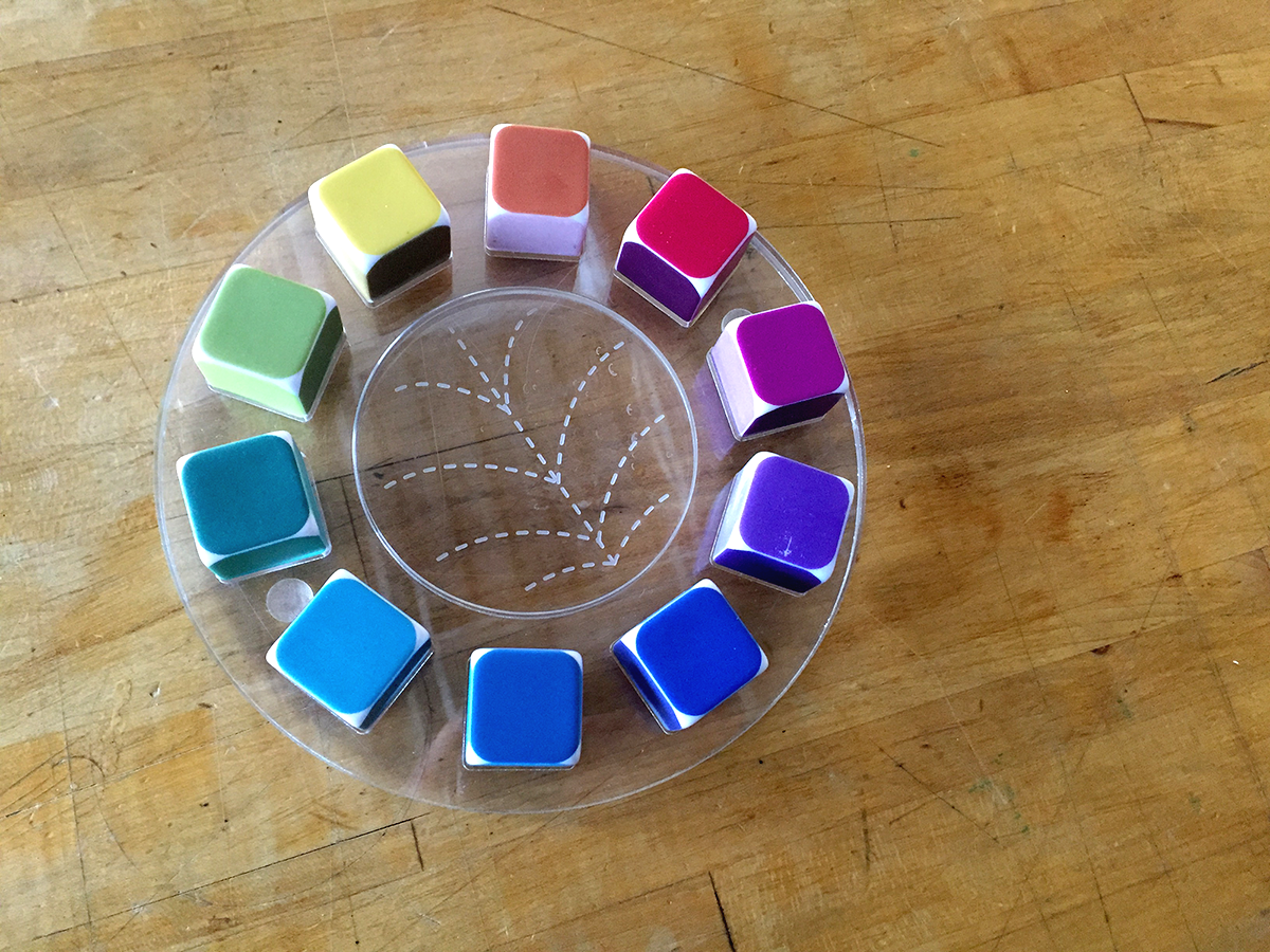 a color wheel, where each color is made of dice. Dice are on a clear plastic tray, with lines at the center to show color relationships like triads and split complementaries.