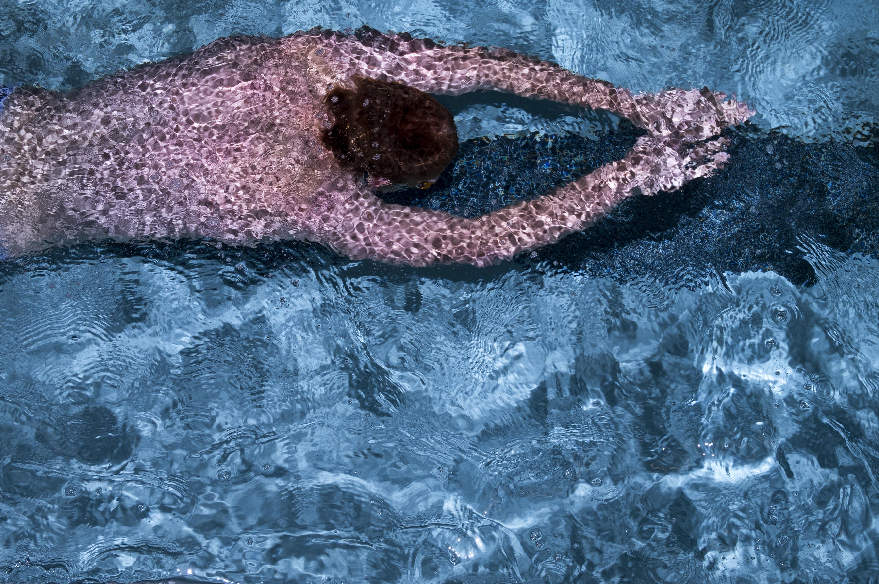A photograph of a man in a speedo swimming in a pool with his arms in front of him, shot from above.