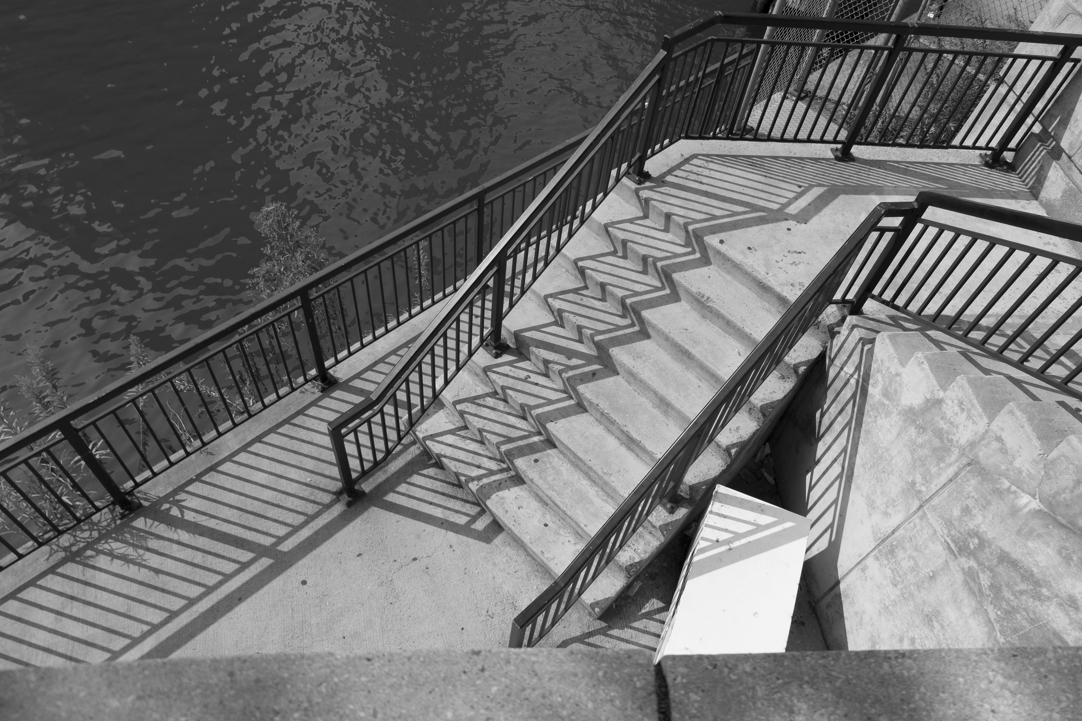 A photograph of a staircase down to a riverside. The stair railings are casting stark shadows on the stairs.