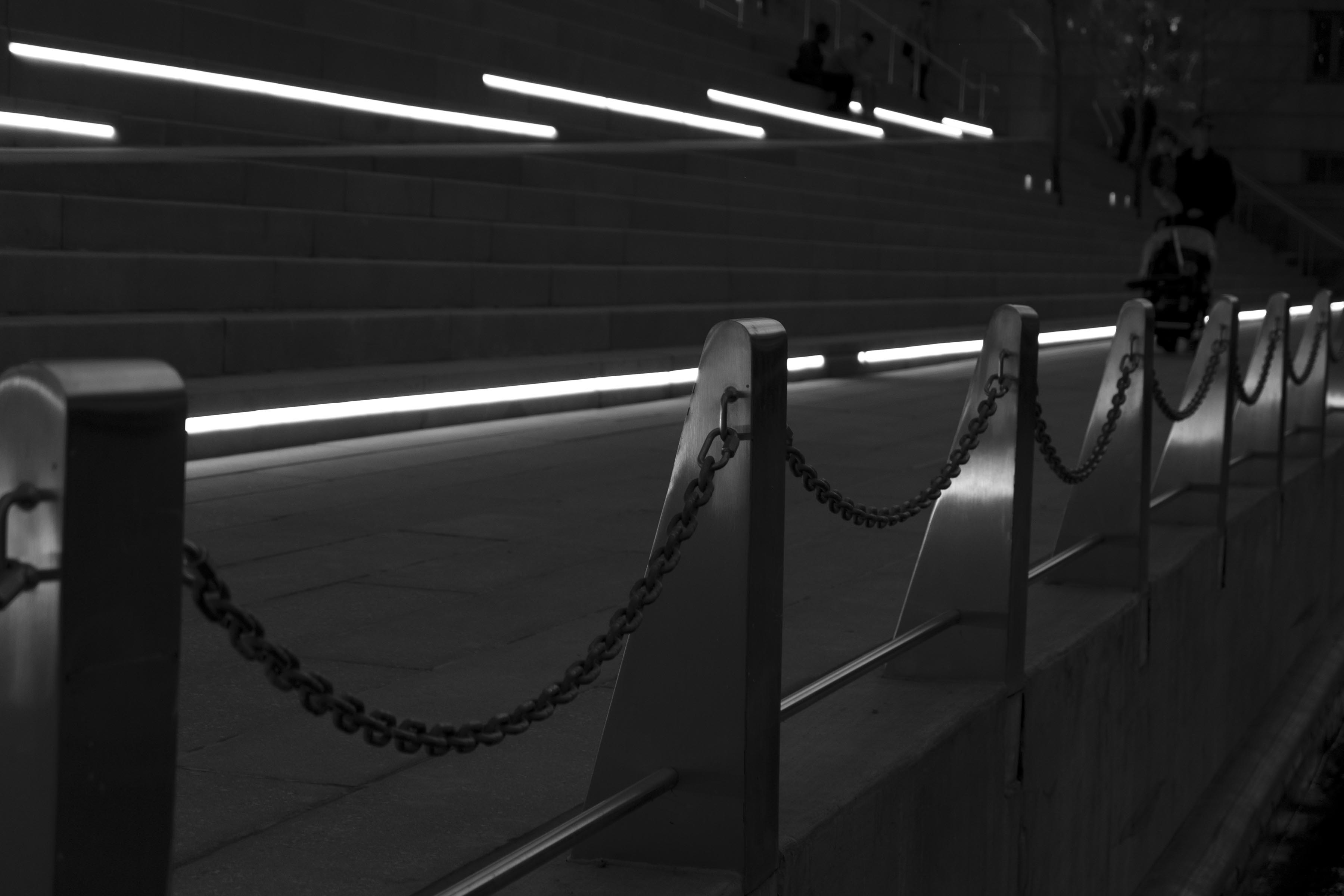 A dark photograph of a chain railing along the riverfront, with bars of bright light on staircases in the background. Perspective disappears into the right background.