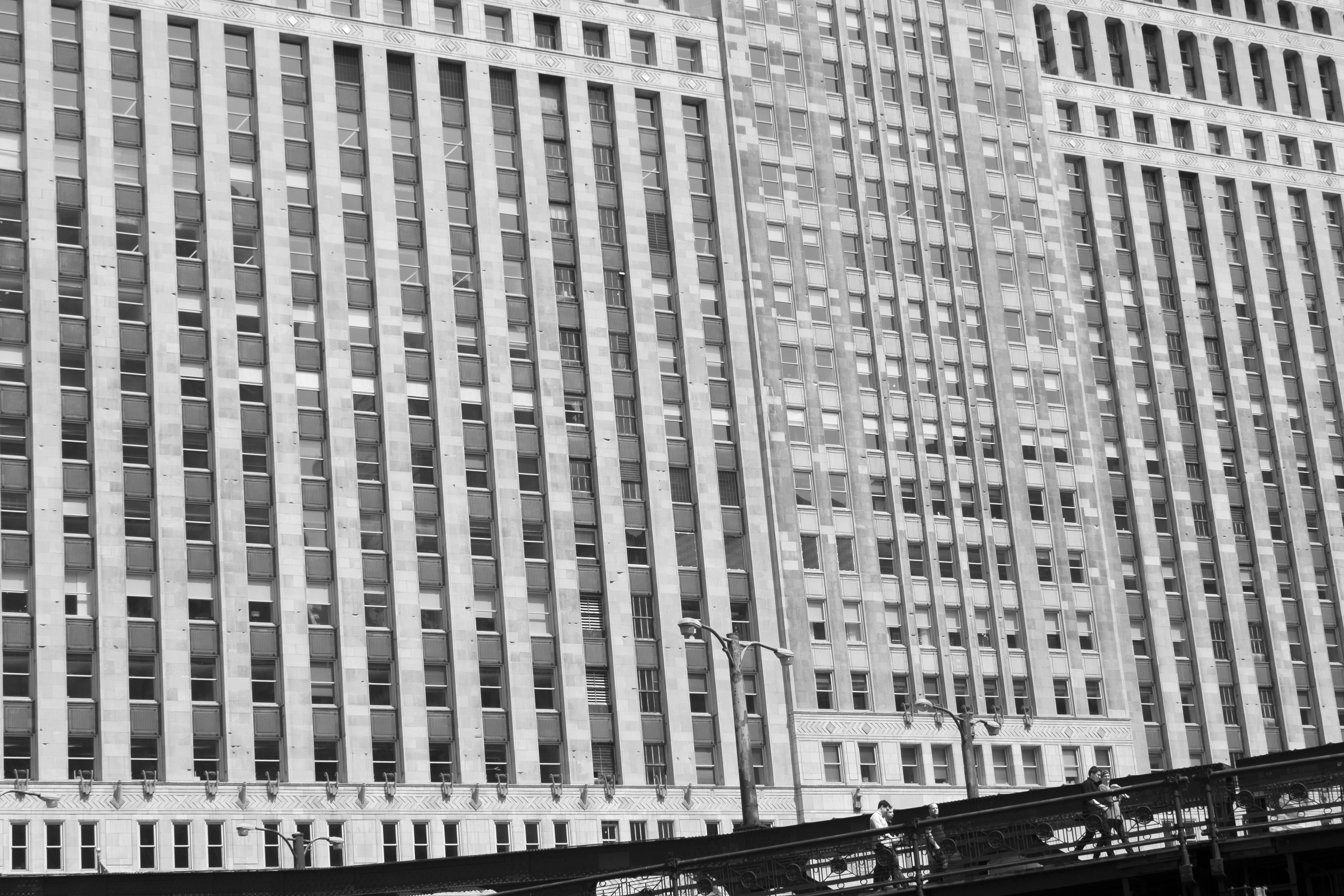 A photograph of a massive building facade with a grid of windows. The right bottom corner of the photograph features a sliver of dark bridge, with 3 small human figures walking on it.